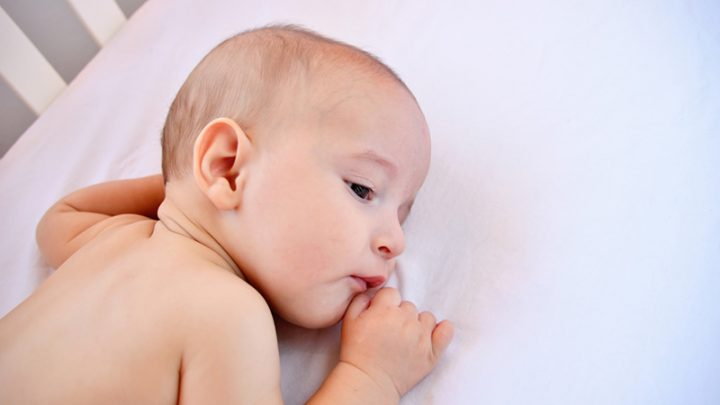 cute baby boy lying on white sheet in crib and sucking lip