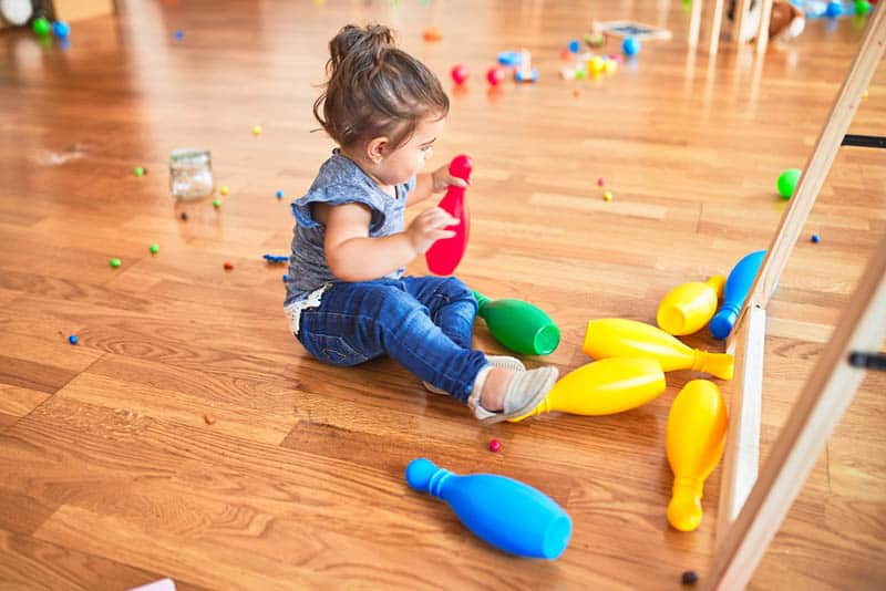 beautiful toddler sitting on the floor and playing with skittles
