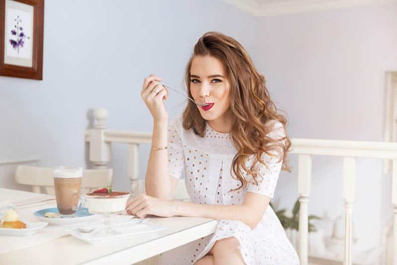 beautiful young woman eating a cake slice