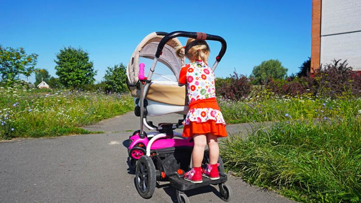 cute little girl standing on a stroller in the park