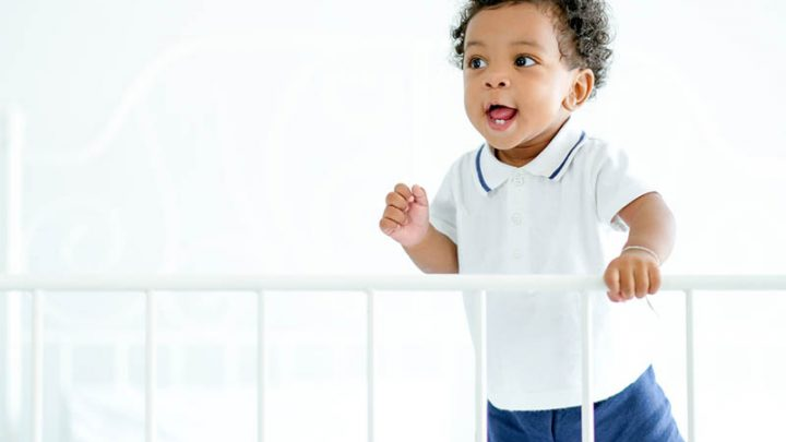 toddler boy standing in bed holding a bed rail