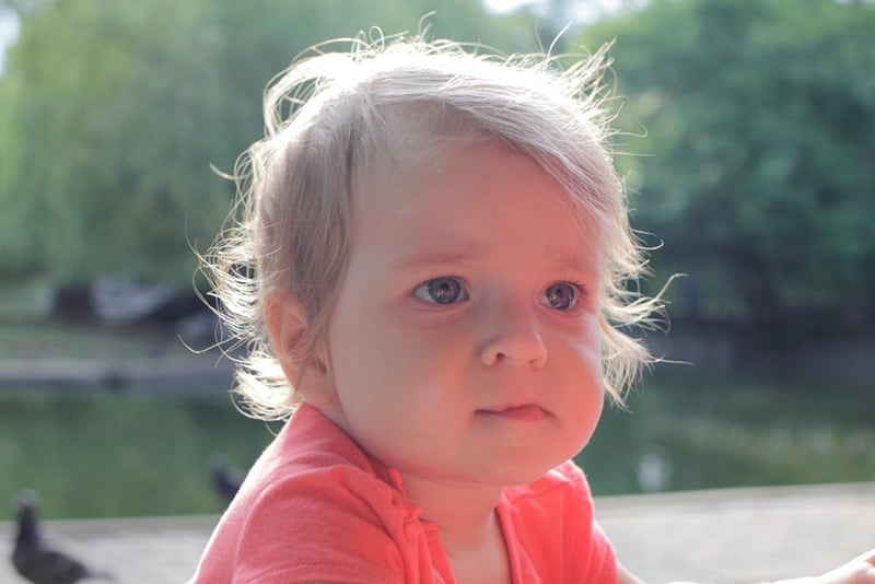 blond baby girl biting her lip and looking at distance outdoor