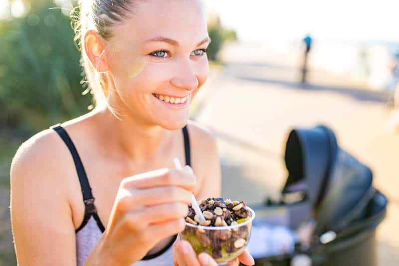 blonde woman holding yogurt ice cream with cocoa bean and peanuts