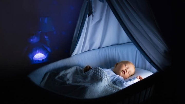 cute baby sleeping at night in a baby bassinet in a room