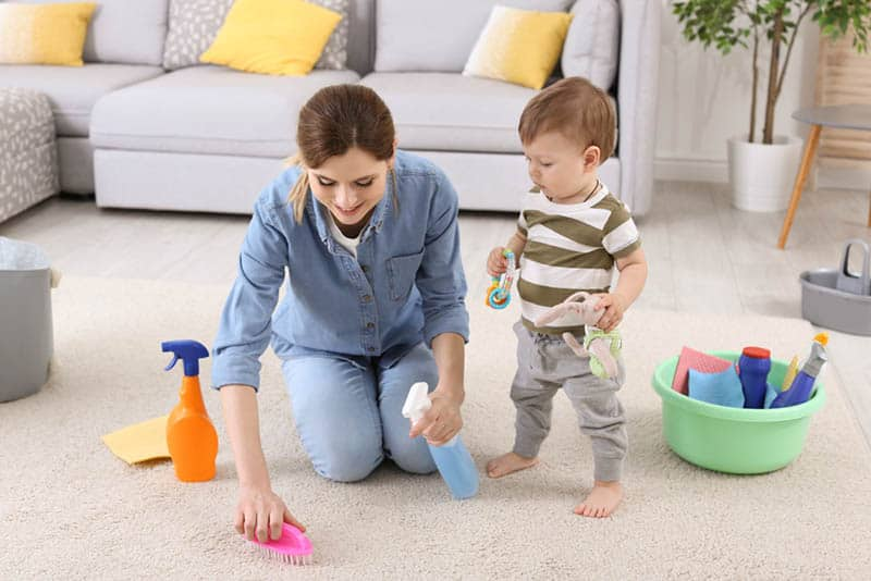 cute baby boy helping mother with cleaning
