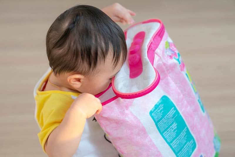 cute baby looking into bag for things to play