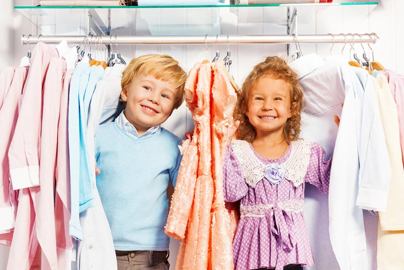 cute boy and a girl playing in wardrobe between the kids clothes