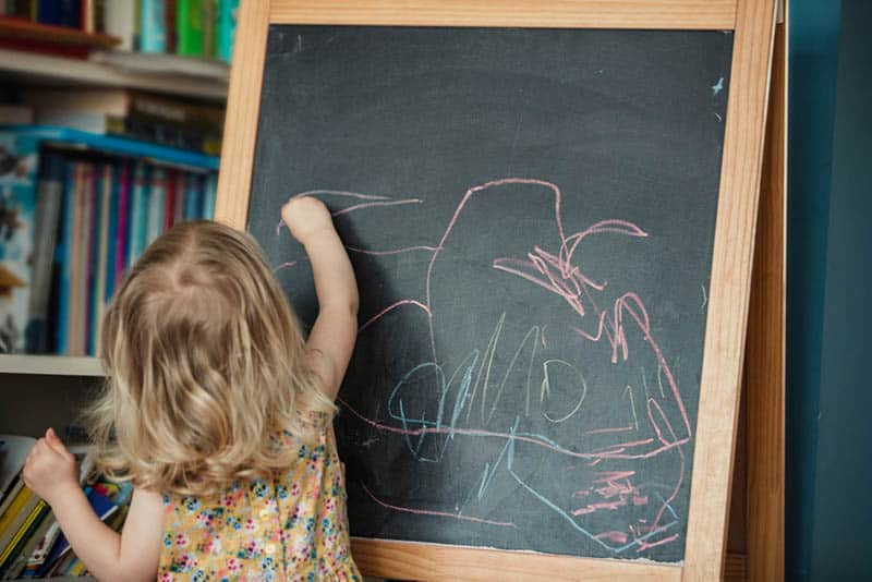 cute little girl drawing with chalk on the board