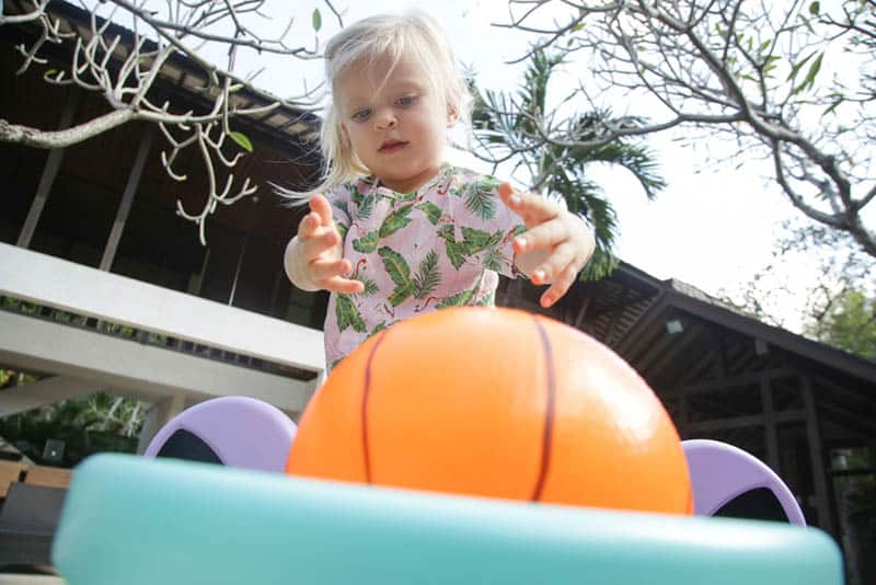 cute little girl playing with plastic basketball ball