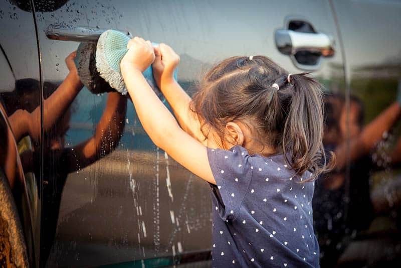 cute little girl washing a car