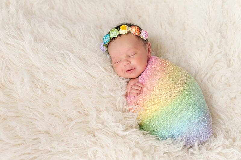 cute newborn baby wrapped into colorful blanket with flower crown on the head