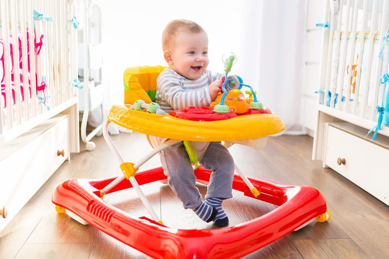cute smiling baby sitting in colorful walker in the room