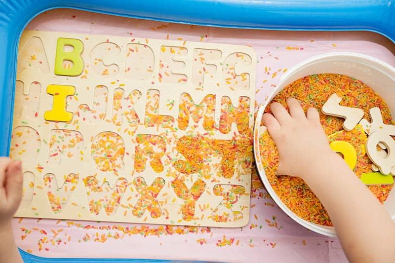 early education for toddlers with colored rice and wooden letters