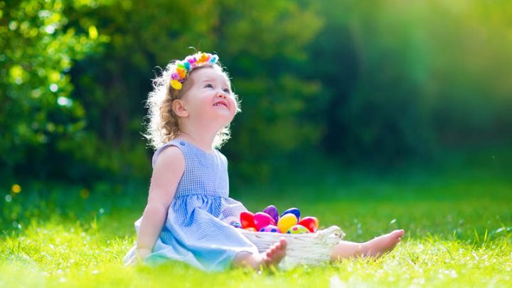 cute baby girl sitting on grass with easter eggs in basket