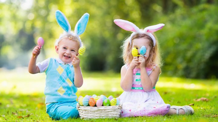 adorable boy and girl playing with easter eggs outdoors