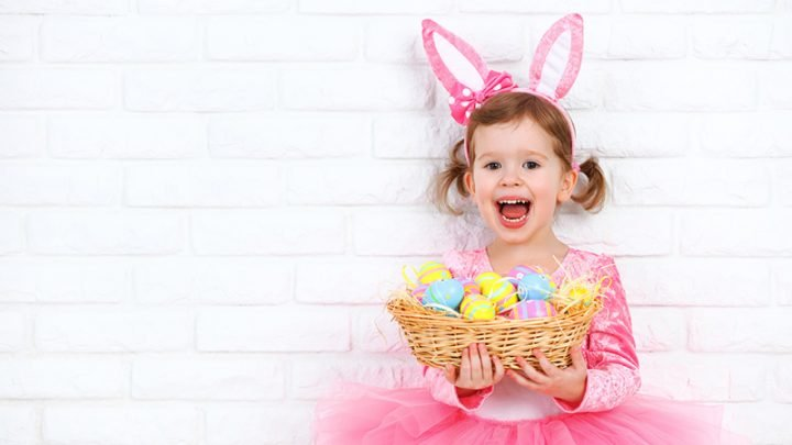 cute baby girl holding easter eggs in a basket