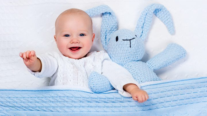 cute baby boy lying in bed with bunny toy and blue blanket