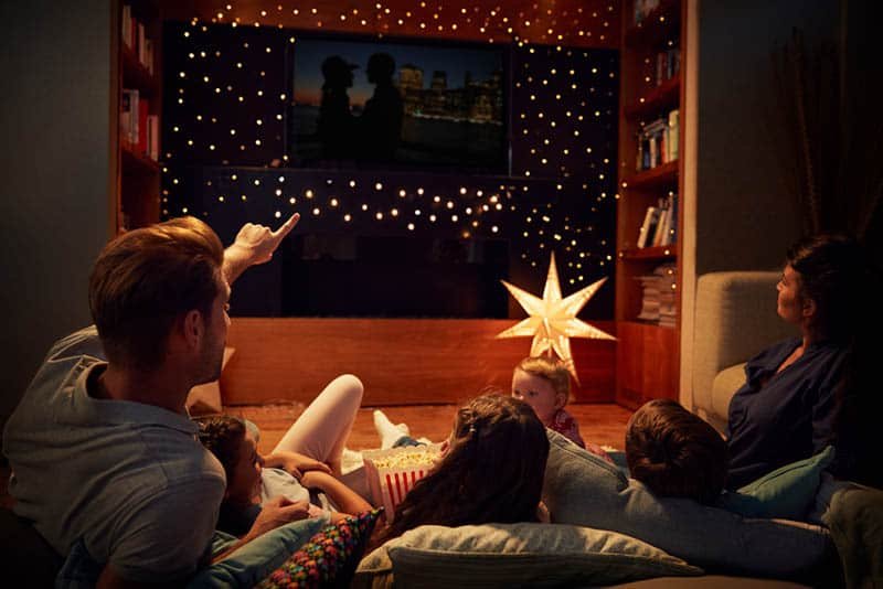 family lying on the floor and watching a movie together