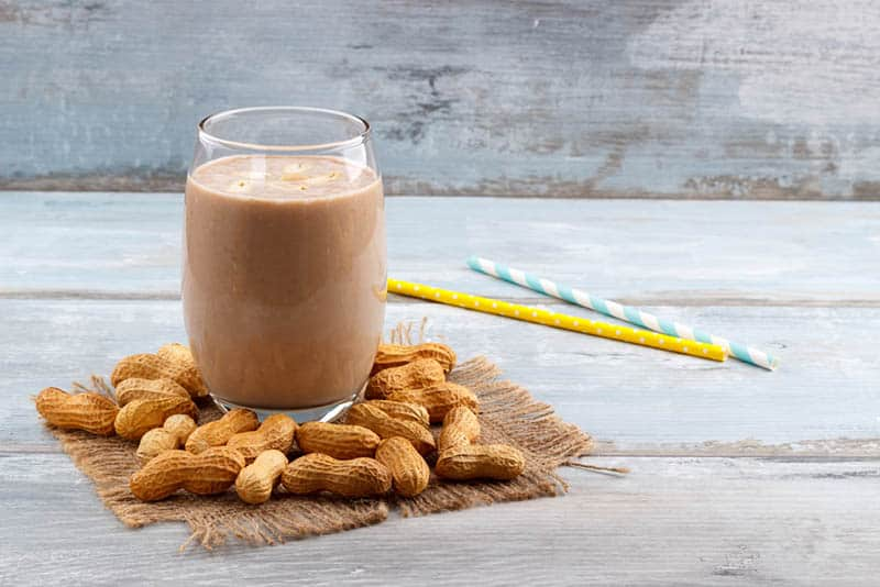 glass of peanut butter smoothie and peanut on the table