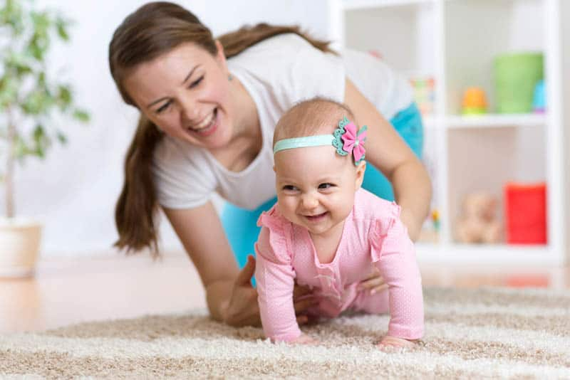 happy mother catching her baby crawling on the floor