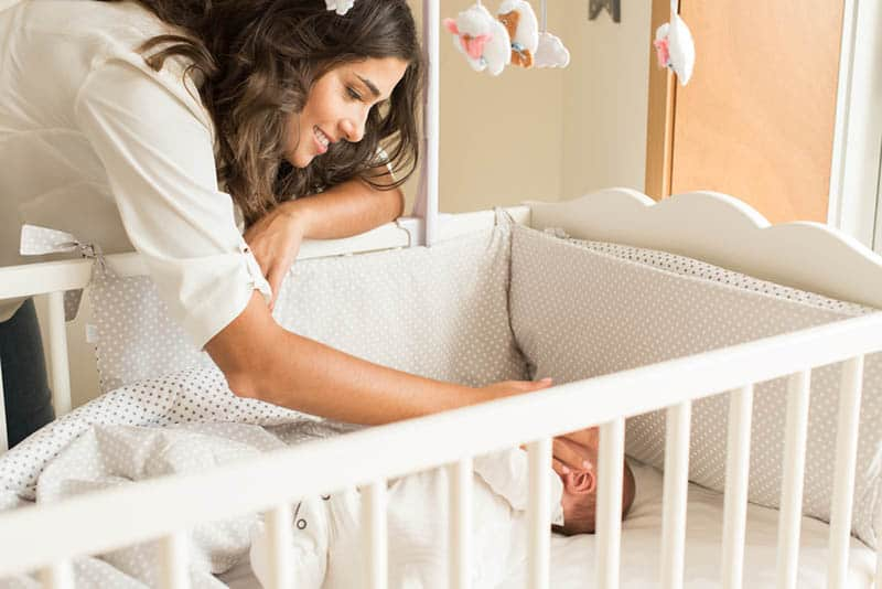 happy mother placing baby to sleep in crib