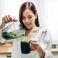 smiling woman putting green smoothie in the glass