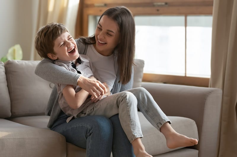 little boy laughing with his mom on the couch