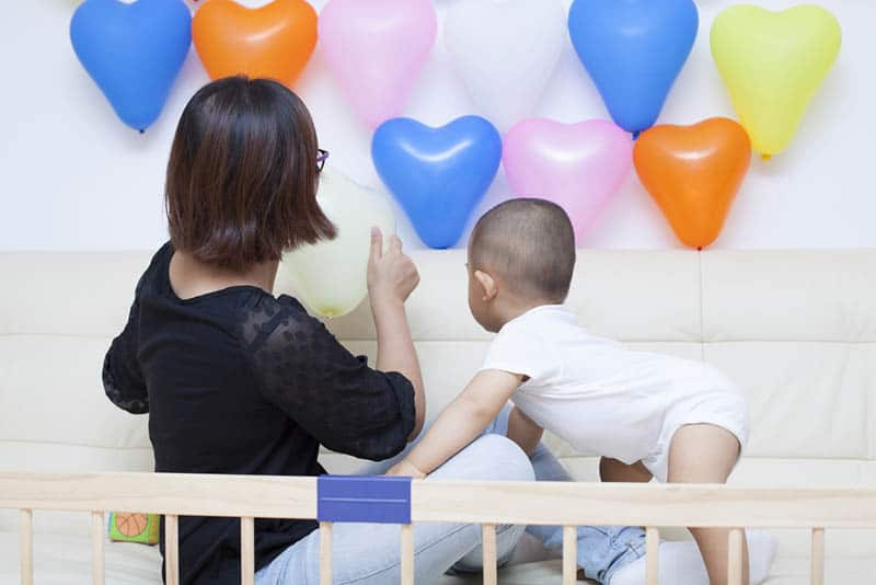 mother and baby boy playing with balloons in the room