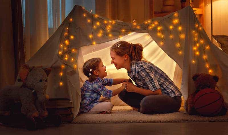 mother and daughter sitting in a tent at home and having fun