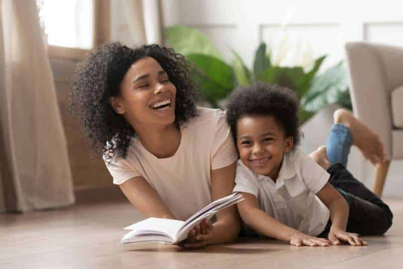 mother and son laughing on the floor with book in hands