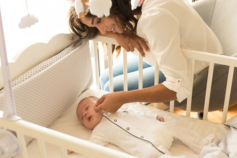 mother cuddling sleeping baby in crib