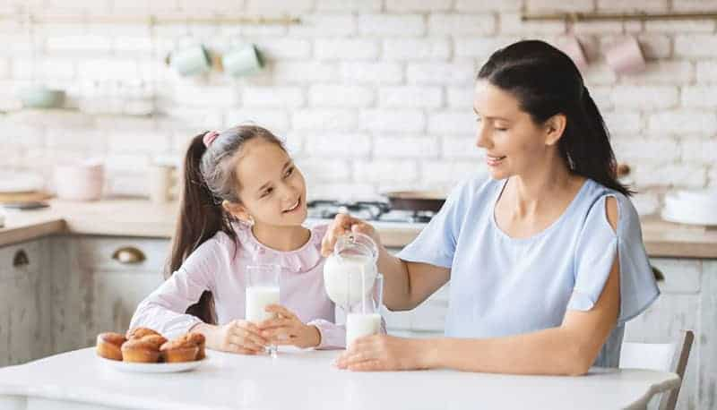 mother getting milk in the glass and talking with daughter in the kitchen