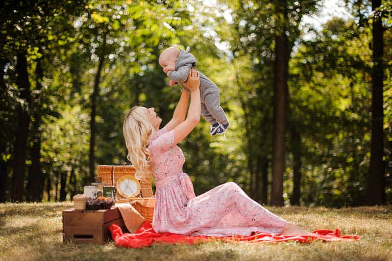 mother playing with baby on picnic in the forest