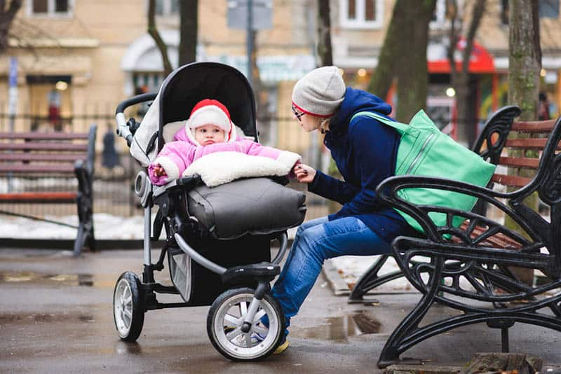 mother sitting on the bench with baby in a stroller