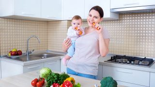 mother with baby eating a carrot in the kitchen