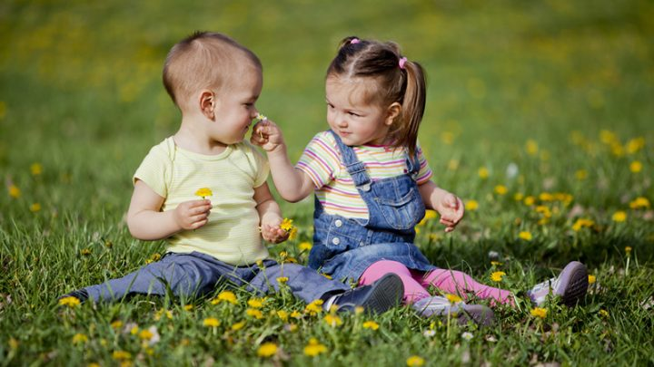 cute girl and a boy playing on the grass with flowers