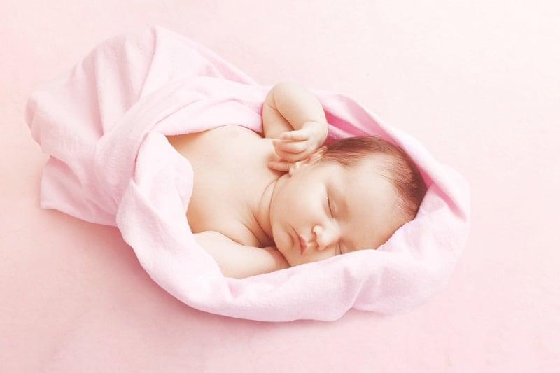 newborn baby sleeping in a pink blanket