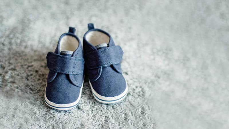 photo of little baby shoes on the grey carpet