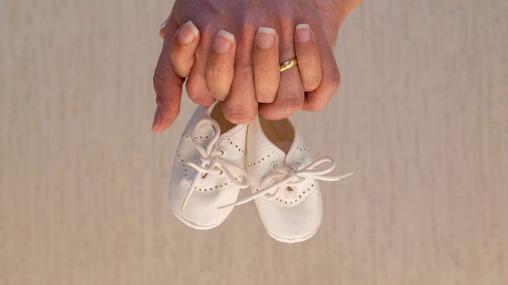 future mother and father holding hands and baby shoes