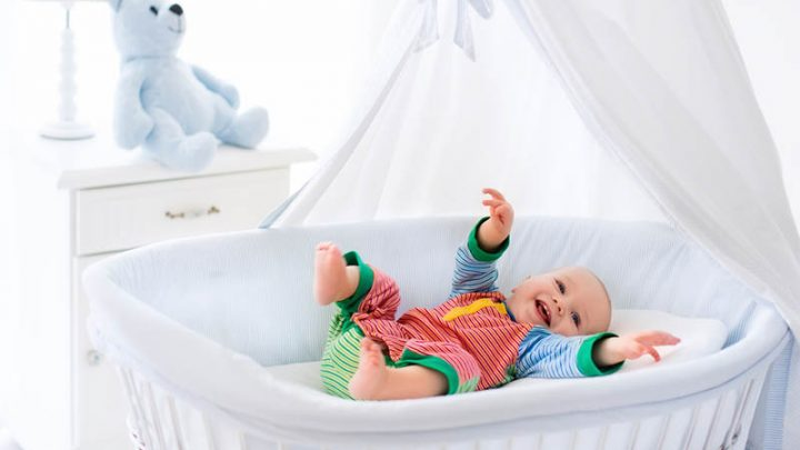 cute baby boy in colorful pajama lying in bassinet