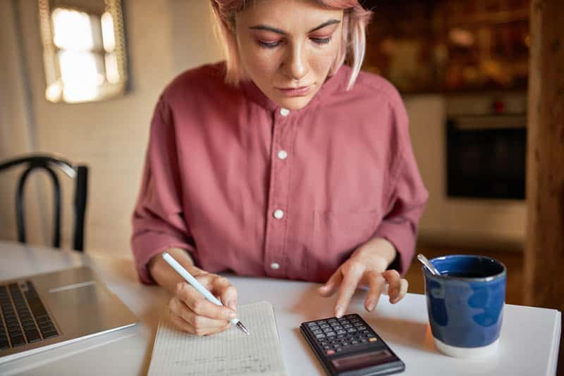 serious woman planning money budget and writing it down