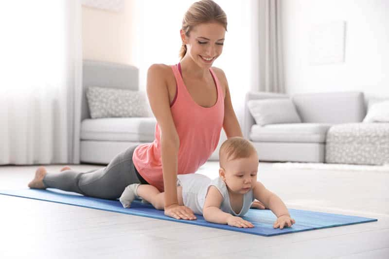 smiling mother doing yoga with baby at home