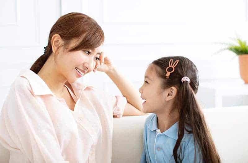 smiling mother looking and listening to her cute daughter