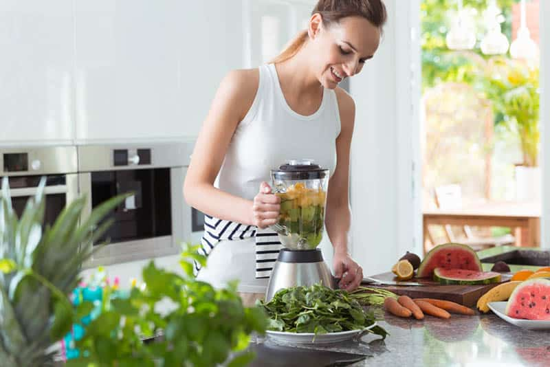 smiling woman making smoothie from fresh fruits and vegetables