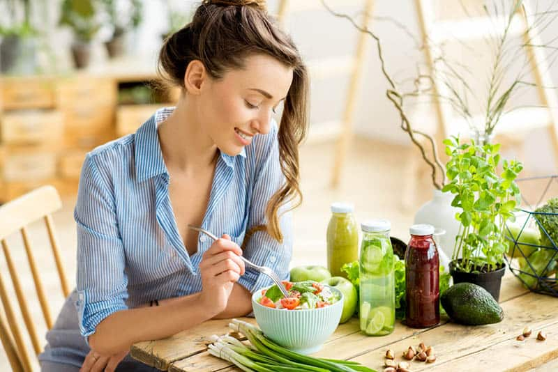 smiling woman sitting by the table and eating vegetables
