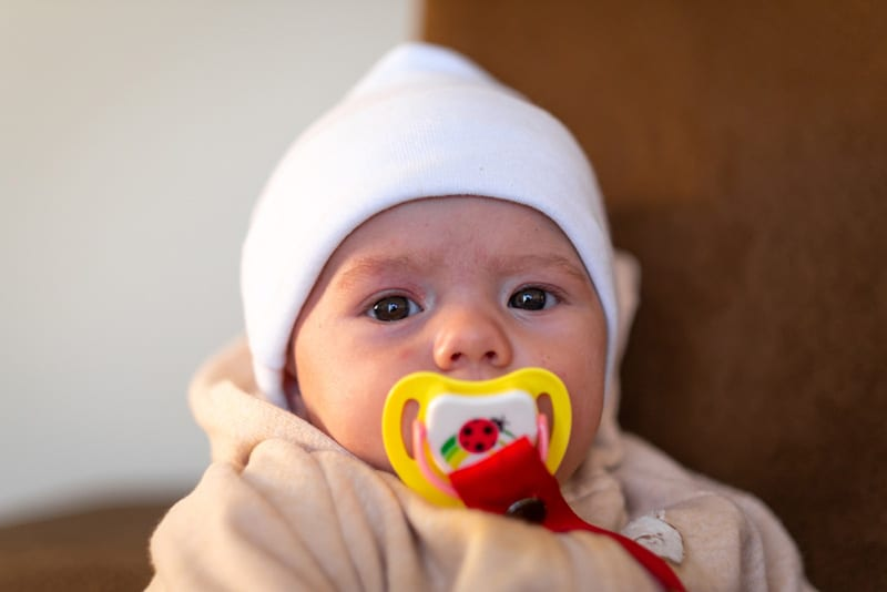 staring baby wearing white winter hat and colorful pacifier