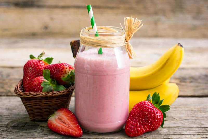 strawberry and banana smoothie in the jar with fresh strawberries and bananas