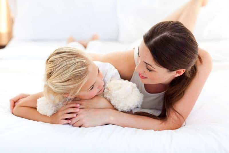 sweet mother and daughter talking on the bed