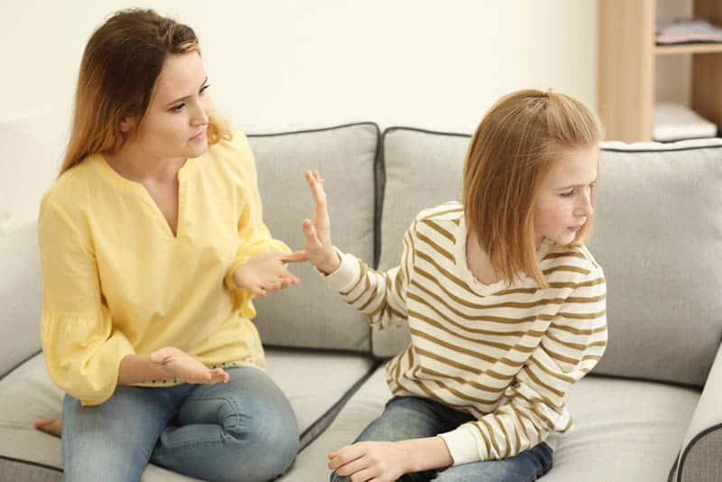teenager girl refusing to talk with mother at home