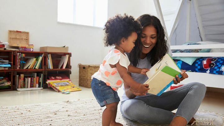 mother reading with baby girl in a room